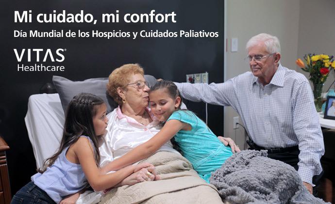 """Una mujer en su cama abraza a dos nietas mientras su esposo las mira, con las palabras """"Mi cuidado, mi confort: Día Mundial de los Hospicios y los Cuidados Paliativos"""" en la imagen"""